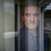 "Martin Gallagher, who was 12 when he was first sexually abused by Rev. Eugene Greene, looks through the window of his home in Gortahork, County Donegal, Ireland. ""There's something there that's never going to go away"", he said in an interview. ""You try to forget, but you can't. It's a thing you just need to have to live with, work around""."