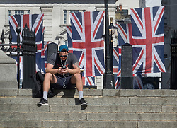 © Licensed to London News Pictures. 04/05/2018. London, UK. A man sits on steps near The Mall in sight of Royal Wedding Union flags on display in the sunshine. High temperatures are expected to continue throughout the bank holiday weekend. Photo credit: Peter Macdiarmid/LNP