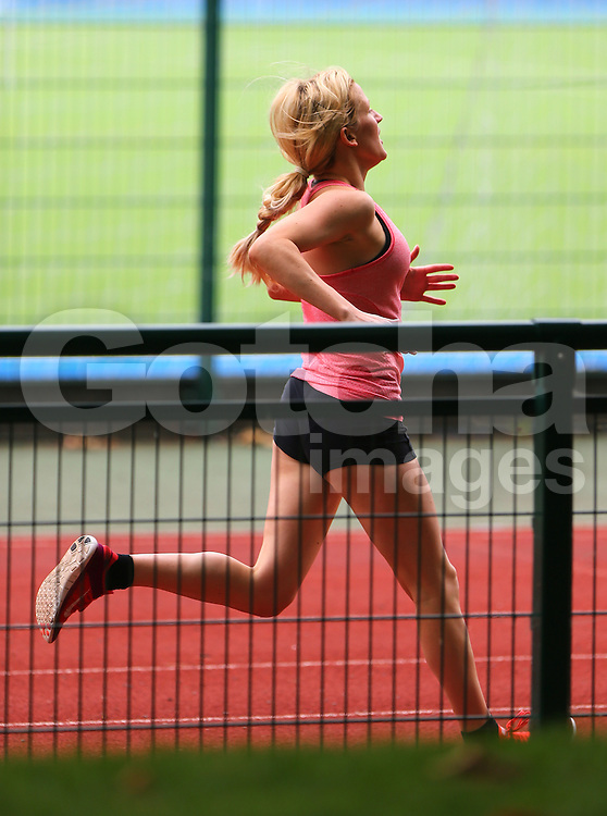 Singer Ellie Goulding keeping fit whilst working out in a London park with a personal trainer.  The 'Burn' singer wearing black shorts a waterproof jacket over a pink strap top and trainers, was seen sprinting on the track and field and also using the climbing apparatus. London. UK. 04/09/2014<br /> BYLINE MUST READ : JAMESY/GOTCHA IMAGES<br /> <br /> Copyright by &copy; Gotcha Images Ltd. All rights reserved.<br /> Usage of this image is conditional upon the acceptance <br /> of Gotcha Images Ltd, terms and conditions available at<br /> www.gotchaimages.com