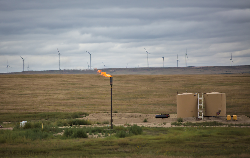 Fracking industry site in Colorado next to a wind farm. Wind turbines share the landscape with a flare at a drill site in Colorado.