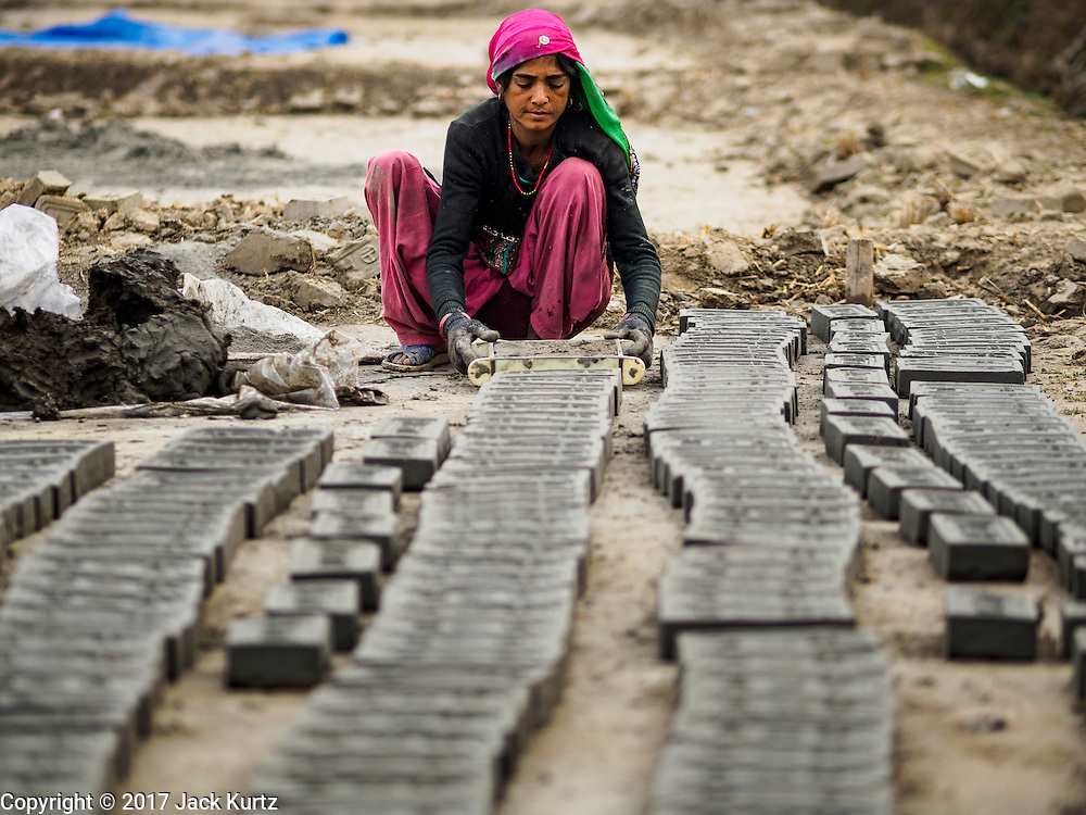 03 MARCH 2017 - BAGMATI, NEPAL: A woman uses a mold to form bricks from clay at a brick factory in Bagmati, near Bhaktapur. There are almost 50 brick factories in the valley near Bagmati. The brick makers are very busy making bricks for the reconstruction of Kathmandu, Bhaktapur and other cities in the Kathmandu valley that were badly damaged by the 2015 Nepal Earthquake. The brick factories have been in the Bagmati area for centuries because the local clay is a popular raw material for the bricks. Most of the workers in the brick factories are migrant workers from southern Nepal.       PHOTO BY JACK KURTZ