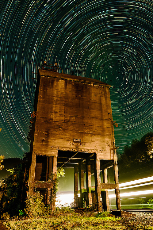 Star trails above the old coaling tower once used to replenish the coal bunkers that would fuel the steam locomotives that came through Thurmond, West Virginia.  A train passes on the right in the background.