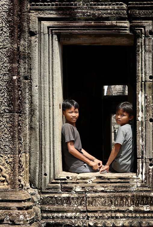Angkor Thom: Bayon temple: two Cambodian boys looking out one of the temple window embrasures, gazing at the camera as they are seated on the sill.
