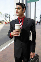 Business man holding take-out coffee cup on city street
