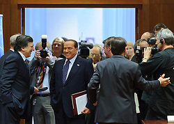 Silvio Berlusconi, Italy's prime minister, center, speaks with Jose Manuel, Barroso, president of the European Commission, left as they arrive for an emergency EU Summit to solve Europe's debt crisis at the European Council headquarters in Brussels, Belgium, on Wednesday, Oct. 26, 2011. (Photo © Jock Fistick)