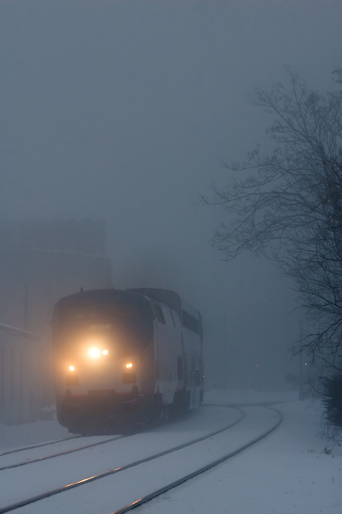 Cutting through thick fog, Amtrak's Texas Eagle speeds through downtown Lemont, IL.