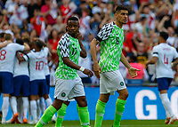 Football - 2018 International Friendly (pre-World Cup warm-up) - England vs. Nigeria<br /> <br /> Leon Balogun (Nigeria) encourages his team after conceding as England celebrate in the background at Wembley Stadium.<br /> <br /> COLORSPORT/DANIEL BEARHAM