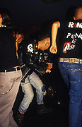 A punk in jeans and black leather jacket amidst other dancers, U.K, 1990s.