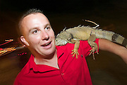 The notorious Full Moon Party at Hat Rin beach on the small Thai island of Ko Pha-Ngan is Asia's biggest regular rave event. Tourist taking souvenir shot with an iguana.