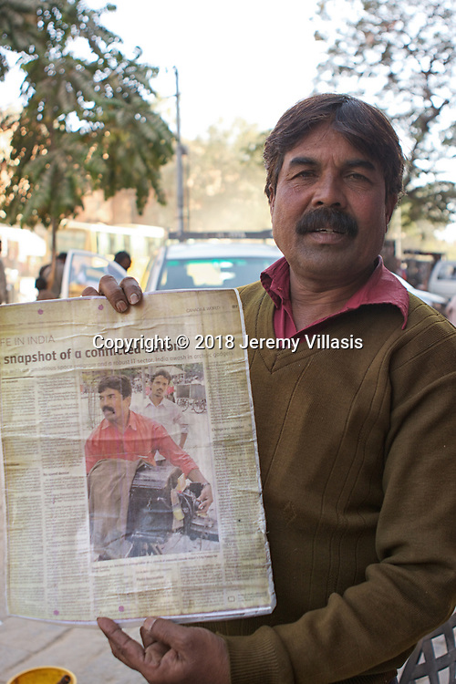 Tikam Chand, the owner of an 1860 Carl Zeiss camera – the last of its kind in the world today, proudly shows off a newspaper article about him to his customers.