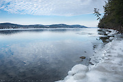 """Otsego Lake, Central New York.    Not far above Cooperstown, I found a place and made my way down to the shore of the lake.  It has been unseasonably warm.  The trees have given up their winter grip, and the ice along the shoreline has been refrozen several times over.  It's mild again today, here at Fairy Spring.  The place is named for the water that bubbled up under Natty Bumpo's house, in James Fenimore Cooper's book 'The Pioneers"""".  But on this particular day, maybe we could say the whole scene is a fairy spring--a tenuous interlude in winter that teases us with the promise of the season to come.  It is here in spirit, but it won't last.  I've felt that false spring so often--the sense of restlessness, the blossoms of new growth, the heady scents and the freshness of it all.  I feel like I go through cycles of that in every season...foolishly enough. It ends, it always ends.  Whether with summer doldrums of winter snowstorms, a fairy spring seems always doomed.  But I'll take it for today, and hope that when the real season comes back, the feeling remains."""