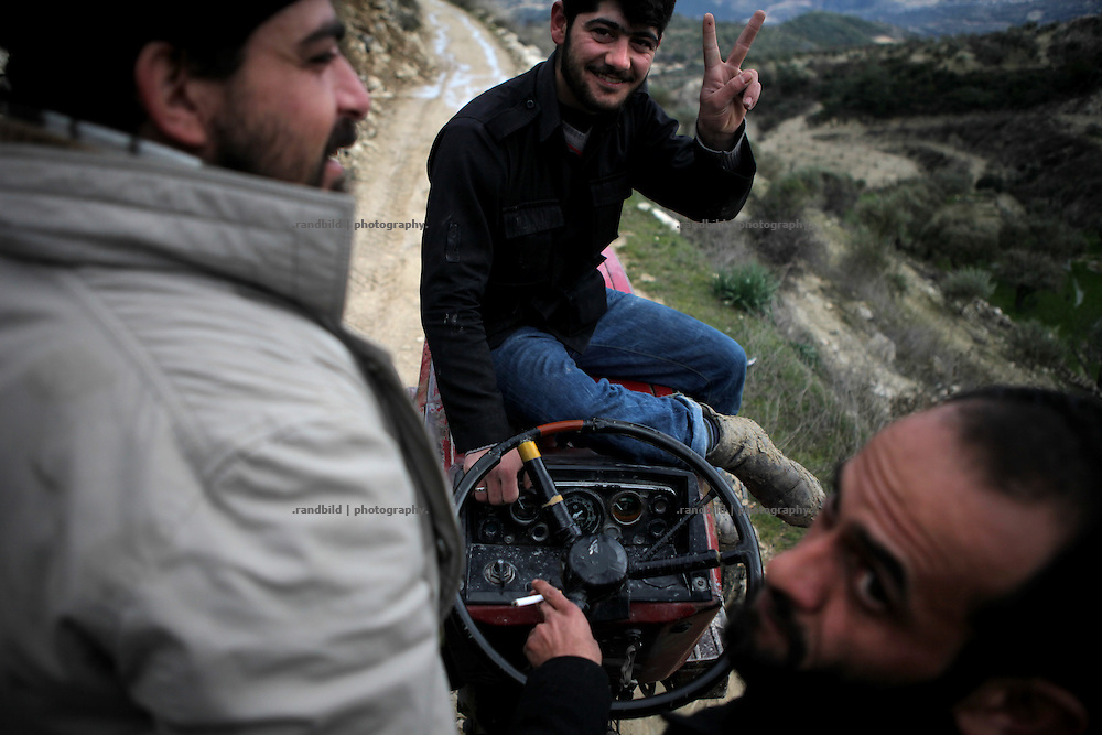 Members of the Free Syrian Army sitting on a tractor on the move to Al Janoudiyah, Province of Idlib, Syria.