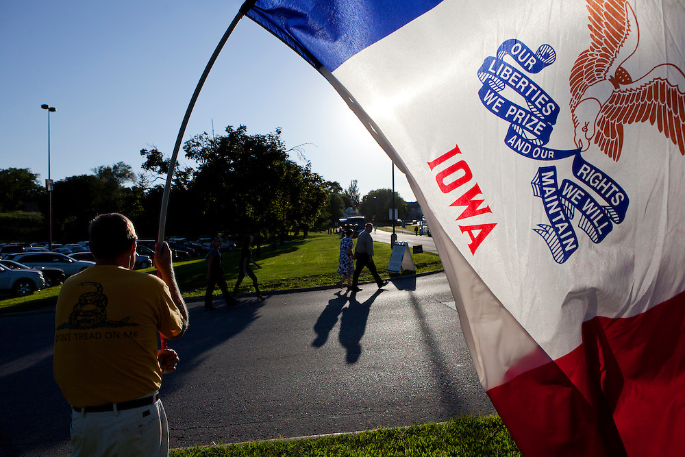 A man holds an Iowa flag outside the Republican presidential debate on Thursday, August 11, 2011 in Ames, IA.