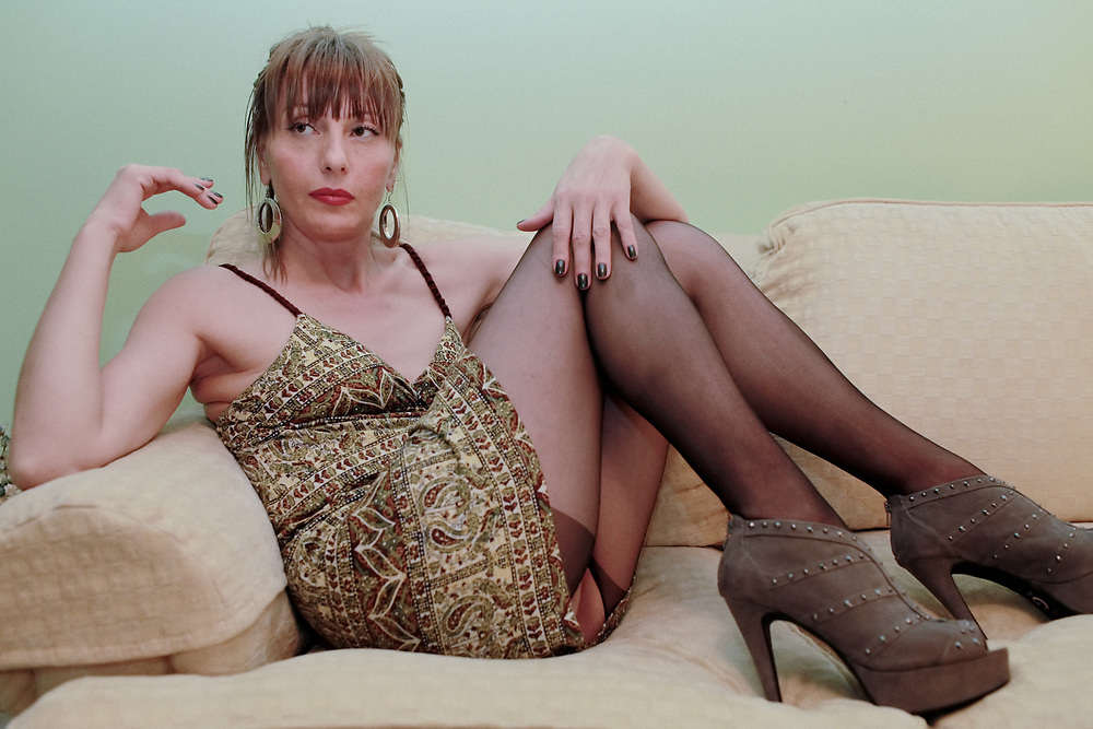 Color portrait blond girl in heels on couch. 2013
