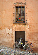 A bicycle parked outside a doorway in the village of Cannobio, Italy. http://www.gettyimages.com/detail/photo/bicycle-and-building-exterior-cannobio-royalty-free-image/482867919