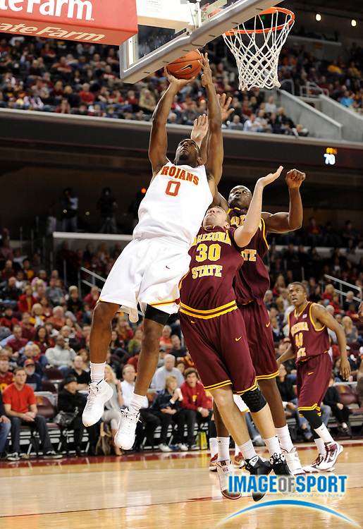Jan 2, 2010; Los Angeles, CA, USA; Southern California Trojans forward Marcus Johnson (0) is defended by Arizona State Sun Devils guard Rihards Kuksiks (30) and center Eric Boateng (2) at the Galen Center. USC defeated Arizona State 47-37.