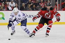 Mar 23; Newark, NJ, USA; Toronto Maple Leafs defenseman John-Michael Liles (24) and New Jersey Devils left wing Ilya Kovalchuk (17) battle for the loose puck during the second period at the Prudential Center.
