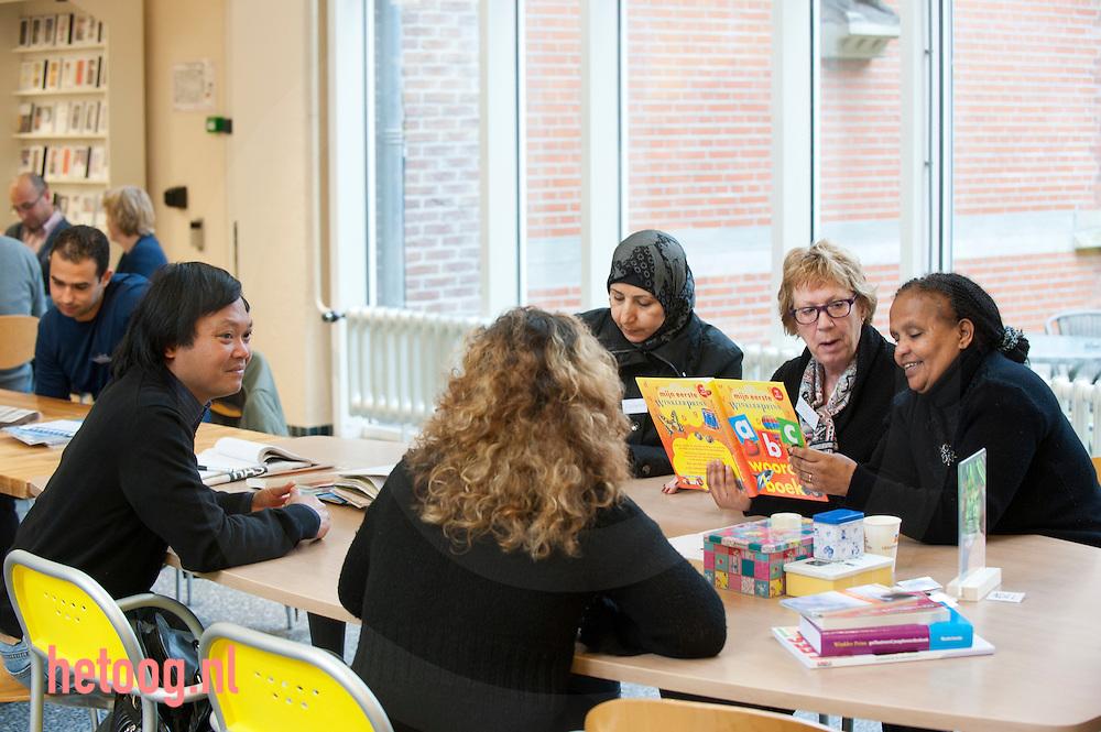 nederland, zwolle 30maart2012 Elke vrijdagochtend van 9.00 tot 11.00 is er in de bibliotheek aan de Diezerstraat een Taalcafé voor anderstaligen die graag Nederlandse conversatie willen oefenen Het Taalcafé is een initiatief van Gilde Zwolle. Dit project startte in 2010 in wijkcentrum de Bestevaer. De bibliotheek heeft eind vorig jaar het Biebcafé hiervoor ter beschikking gesteld..Een mooie locatie met heel veel boeken, tijdschriften en kranten en dus voldoende inspiratie voor boeiende gespreksonderwerpen. De ruimte bevalt goed en het deelnemersaantal neemt nog steeds toe...Taalcafé werkt met een enthousiast team van vrijwilligers. In groepjes van 3-5 personen wordt onder leiding van een vrijwilliger gesproken over allerlei onderwerpen variërend van.het weer, gezondheidszorg in Nederland tot actuele nieuwsberichten. Ter afwisseling zijn er taalspelletjes en komt er incidenteel een gastspreker vertellen.