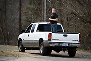 A man stands in the flatbed of his pickup truck along the roadside in Swannanoa, N.C. to view and honor the hearse carrying the body of Rev. Billy Graham as it travels from the Billy Graham Training Center at the Cove in Asheville, N.C. to the Billy Graham Library in Charlotte. N.C.on Saturday, Feb. 24, 2018. (AP Photo/Kathy Kmonicek)