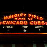 Famous Wrigley Field sign at night with glowing neon. Wrigley Field is home of the Chicago Cubs. High resolution prints and stock photos are available.
