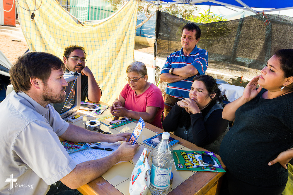 The Rev. Cristian E. Rautenberg, president of the Confessional Lutheran Church of Chile talks to a family living in a tent Wednesday, April 23, 2014, in Alto Hospicio, Chile. The family's home was damaged from a magnitude 8.2 earthquake on April 1, 2014 approximately 95km northwest of Iquique. The earthquake condemned several thousand homes and severely damaged more than 10,000 others. LCMS Communications/Erik M. Lunsford