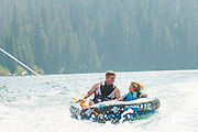 Father and son laugh and smile while tubbing on Red Fish Lake, Stanley, Idaho.