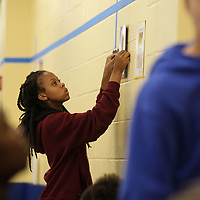 Tupelo Middle School student Jada Mayfield, 14, begins hanging posters around a timeline they are constructing at the schools cafeteria for the state's Bicentennial celebration next week.