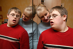 Mother and son standing by mirror on wardrobe,