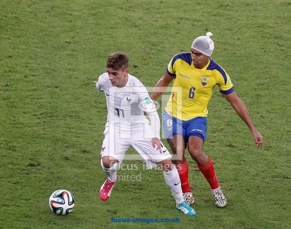 Antoine Griezmann of France (L) goes past Christian Noboa of Ecuador (R who had a head injury in the 1st half during the 2014 FIFA World Cup Group E match at Maracana Stadium, Rio de Janeiro<br /> Picture by Andrew Tobin/Focus Images Ltd +44 7710 761829<br /> 25/06/2014