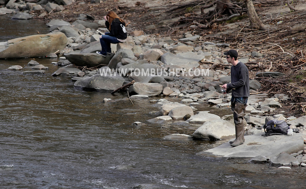 Cornwall, New York - A man fishes in the Moodna Creek while a girl sits on rocks and reads a book on April 3, 2011.