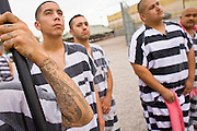 "17 JULY 2006 - PHOENIX, AZ: Inmates stand at attention during the National Anthem in ""Tent City"" in the Maricopa County Jail in Phoenix, AZ. There are about 650 inmates living in the tents. Maricopa County Sheriff Joe Arpaio recently started playing the Star Spangled Banner and God Bless America twice a day in the county jails. Inmates are encouraged, but not forced, to stand at attention with their hands over their hearts, when the music is played. When asked about the new policy Arpaio said, ""Our men and women are fighting and dying for our country in Iraq and that's the least these inmates can do."" In 2011, the US Department of Justice issued a report highly critical of the Maricopa County Sheriff's Department and the jails. The DOJ said the Sheriff's Dept. engages in widespread discrimination against Latinos during traffic stops and immigration enforcement, violates the rights of Spanish speaking prisoners in the jails and retaliates against the Sheriff's political opponents.      PHOTO BY JACK KURTZ"