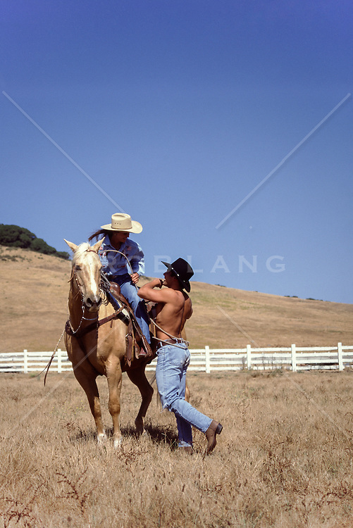 shirtless cowboy and a cowboy on a horse on a ranch