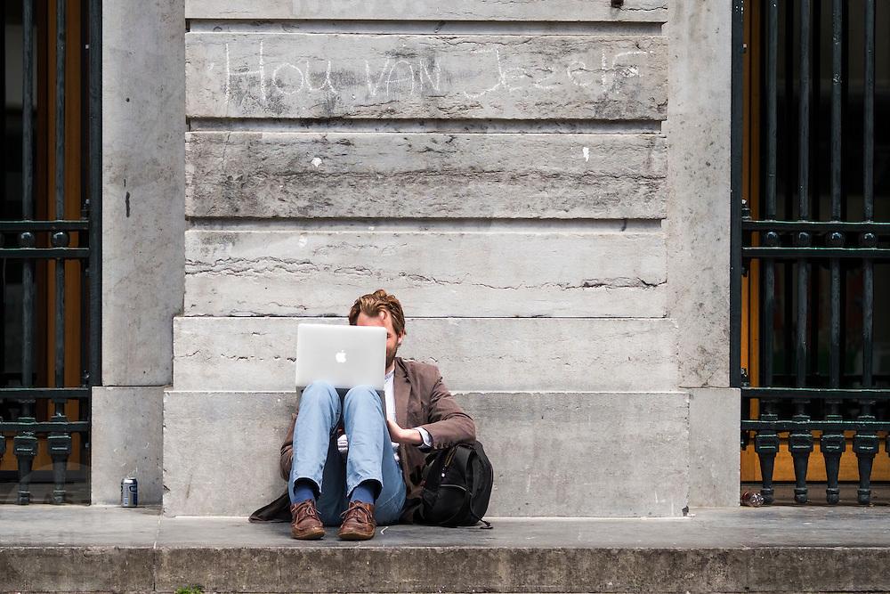 Een man zit voor het stadhuis van Utrecht te werken achter zijn Apple laptop.<br /> <br /> A man is working on his Apple computer outside of the town hall of Utrecht.