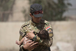 &copy; Licensed to London News Pictures. 15/06/2017. Mosul, Iraq. An Iraqi Army soldier, of 9th Armoured Division, holds a small child as families flee from ISIS held West Mosul.<br /> <br /> Despite heavy fighting between the Islamic State and Iraqi Security Forces many civilians have started to leave ISIS territory in West Mosul. Mosul residents, many of whom have been in hiding in their homes since the start of the West Mosul Offensive, often have to run through ISIS sniper and machine gun fire to reach the safety of Iraqi Security Forces positions. Photo credit: Matt Cetti-Roberts/LNP