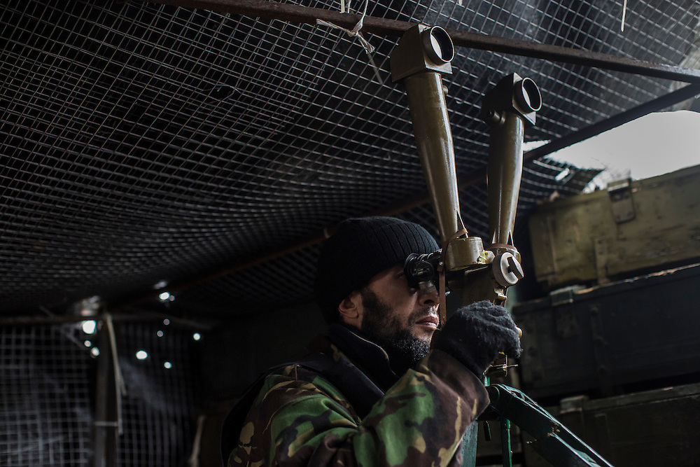 PIKSY, UKRAINE - NOVEMBER 19, 2014: A member of the Dnipro-1 brigade, a pro-Ukraine militia, watches the front line through a trench periscope in Pisky, Ukraine. The village of Pisky is the scene of much of the front-line fighting over the Donetsk airport. CREDIT: Brendan Hoffman for The New York Times