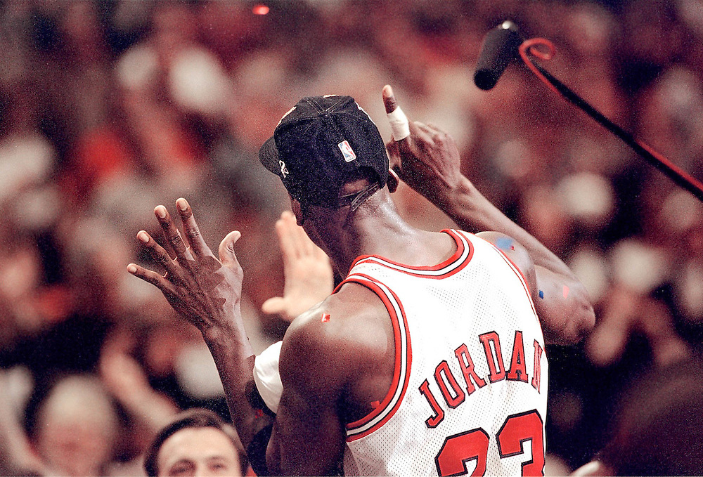 Michael Jordan holds up six fingers indicating the number of NBA Championships he intends to win. This photo was taken during post game celebration after game 6 of the 1997 NBA Finals in Chicago. August Miller photo