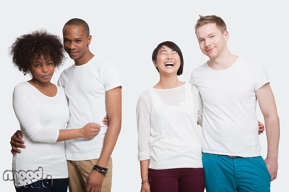 Portrait of two young couples in casuals standing together over white background