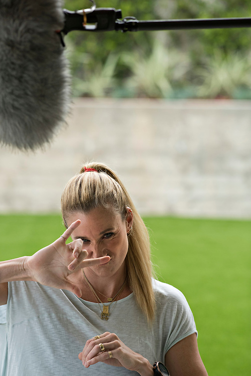 """Kerri Walsh Jennings takes a break from her on-camera interview ESPN's Sportscenter, to signal """"I love you"""" to her oldest son Joey, 8, after he arrived home from school."""
