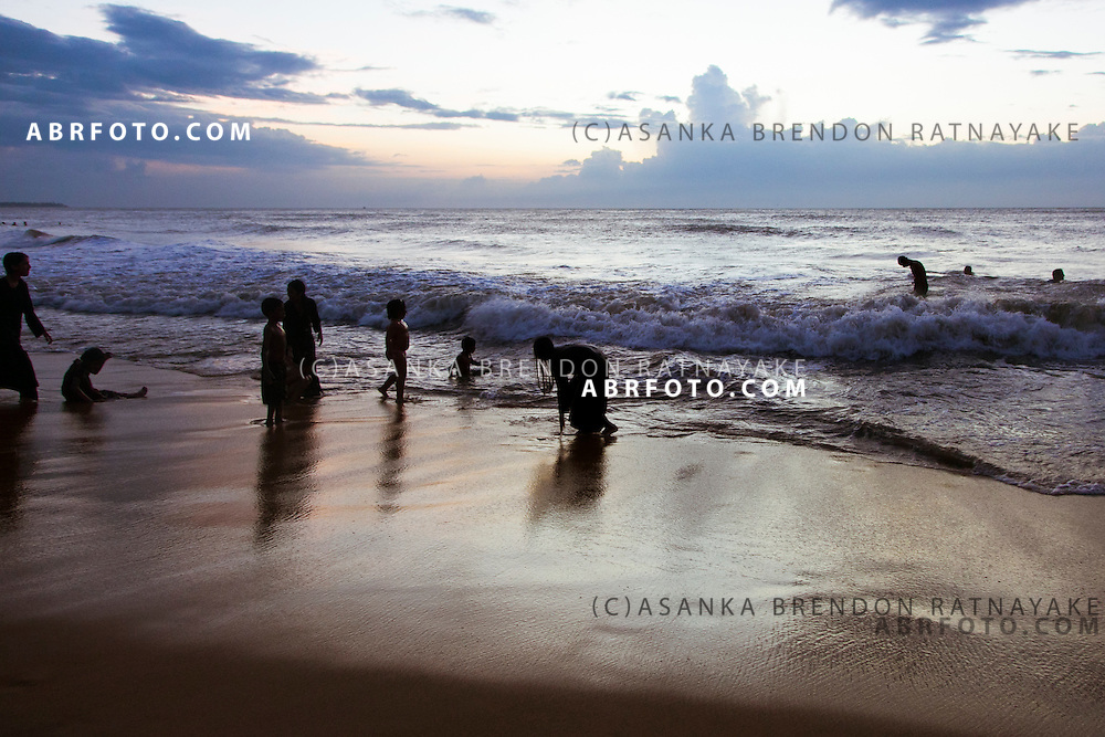 Silhouettes of children playing along the coast line as the sunset at Negombo beach. Negombo is a major city in Sri Lanka, located on the west coast of the island and at the mouth of the Negombo Lagoon
