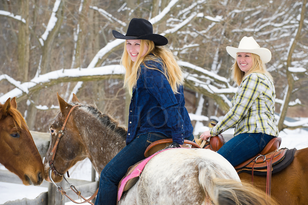 Mounted women horseback riders visit with other horses over a fence, winter with snow falling on tree limbs background, attractive blondes in western apparel with cowboy hats, Pennsylvania, PA, USA.