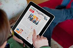 Woman using iPad tablet computer to read Der Tagesspiegel German Berlin daily newspaper online
