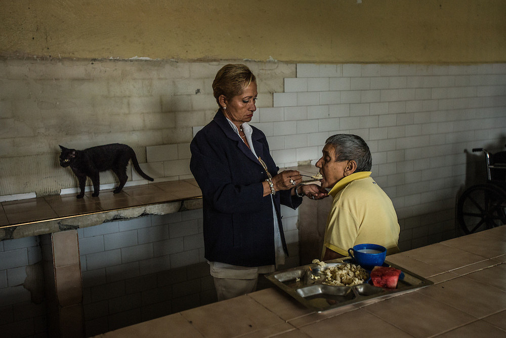 BARQUISIMETO, VENEZUELA - JULY 28, 2016: Head nurse Évila García feeds a patient pasta as a stray cat roams around the women's ward dining hall. The economic crisis that has left Venezuela with little hard currency has also severely affected its public health system, crippling hospitals like El Pampero Psychiatric Hospital by leaving it without the resources it needs to take care of patients living there, the majority of whom have been abandoned by their families and rely completely on the state to meet their basic needs. There is a shortage of food, and the majority of patients have lost a significant amount of weight since the crisis began in 2013. Nurse García said that many patients that are stable enough to be cared for at home, have been abandoned by their families because of the food shortages - by sending their family member to the hospital, it is one less mouth they have worry about feeding.  PHOTO: Meridith Kohut