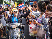"""29 NOVEMBER 2013 - BANGKOK, THAILAND: Office workers in Bangkok """"high five"""" anti-government protestors as they motorcade through Bangkok. Although the government has a popular mandate, most of its supporters are from the rural northeast part of Thailand. Most members of Bangkok's middle class oppose the government. Several thousand Thai anti-government protestors marched on the US Embassy in Bangkok. They blew whistles and asked the US to honor their efforts to unseat the elected government of Yingluck Shinawatra. The anti-government protestors marched through several parts of Bangkok Friday paralyzing traffic but no clashes were reported, even after a group protestors tried to occupy Army headquarters.         PHOTO BY JACK KURTZ"""