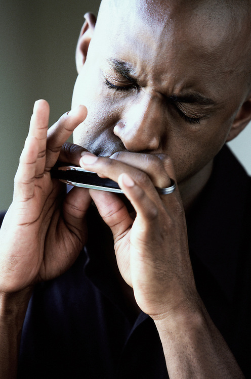 Portrait of man playing harmonica