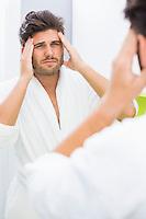 Reflection of man in bathrobe suffering from headache