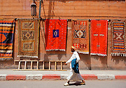 Man walking past Berber carpets for sale on display in the street, Marrakesh, Morocco RESERVED USE - NOT FOR DOWNLOAD -  FOR USE CONTACT TIM GRAHAM