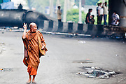 18 MAY 2010 - BANGKOK, THAILAND:  A Buddhist monk flashes the peace sign as he walks through Din Daeng intersection, while others take cover from snipers thought to be in the area in Bangkok Tuesday. The intersection has been under periodic sniper fire from unidentified snipers near Thai military lines. Violent unrest continued in Bangkok again Tuesday nearly a week after Thai troops started firing on protesters and Bangkok residents took to the streets in violent protest against the government. Tuesday was not as violent as previous days however. Although protesters continued to set up roadblocks and flaming tire barricades across parts of the city, there was not as much gunfire from the government lines. The most active protesters were at the Din Daeng Intersection about a mile from the Red Shirts' Ratchaprasong camp.  PHOTO BY JACK KURTZ