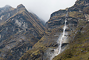 Waterfall and fog, above Deurali village (10,600 feet / 3231 meters elevation), in the deep valley of the Modi Khola river, in the Annapurna Mountain Range of Nepal.