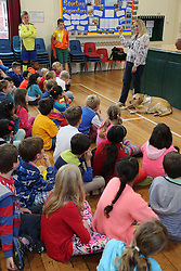 Visually impaired woman with guide dog doing presentation at a primary school.