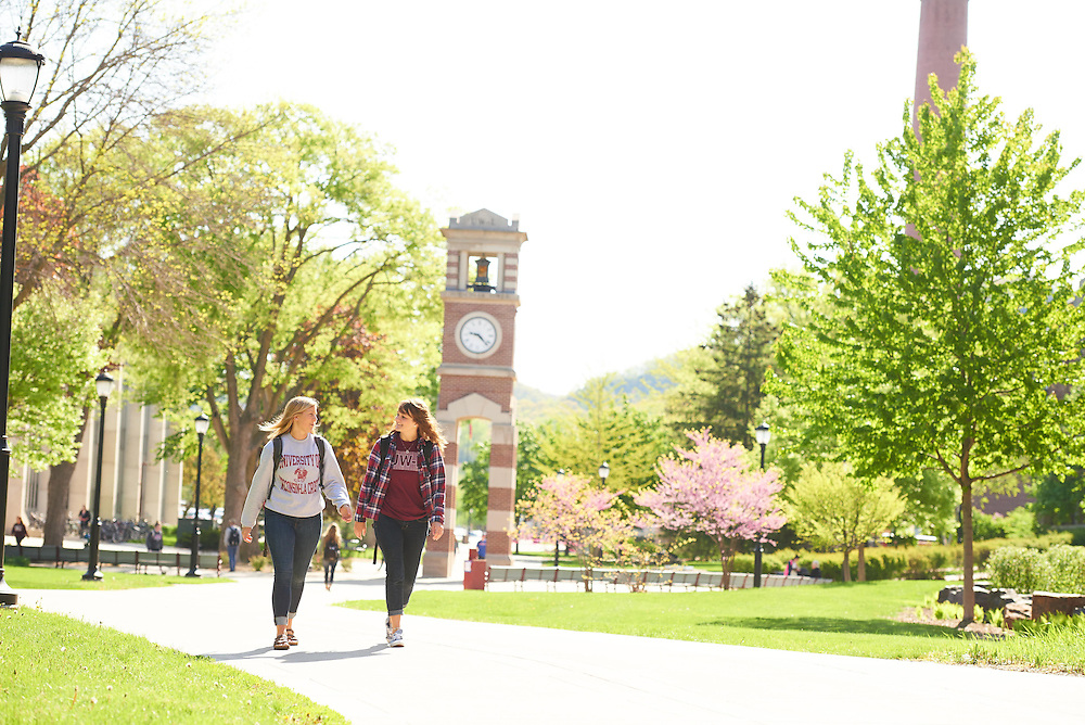 Activity; Walking; Smiling; Buildings; Graff Main Hall; Location; Outside; People; Woman Women; Student Students; Spring; May; Time/Weather; sunny; Type of Photography; Candid; Lifestyle; UWL UW-L UW-La Crosse University of Wisconsin-La Crosse; Clock Hoeschler Tower; Emma Hermes